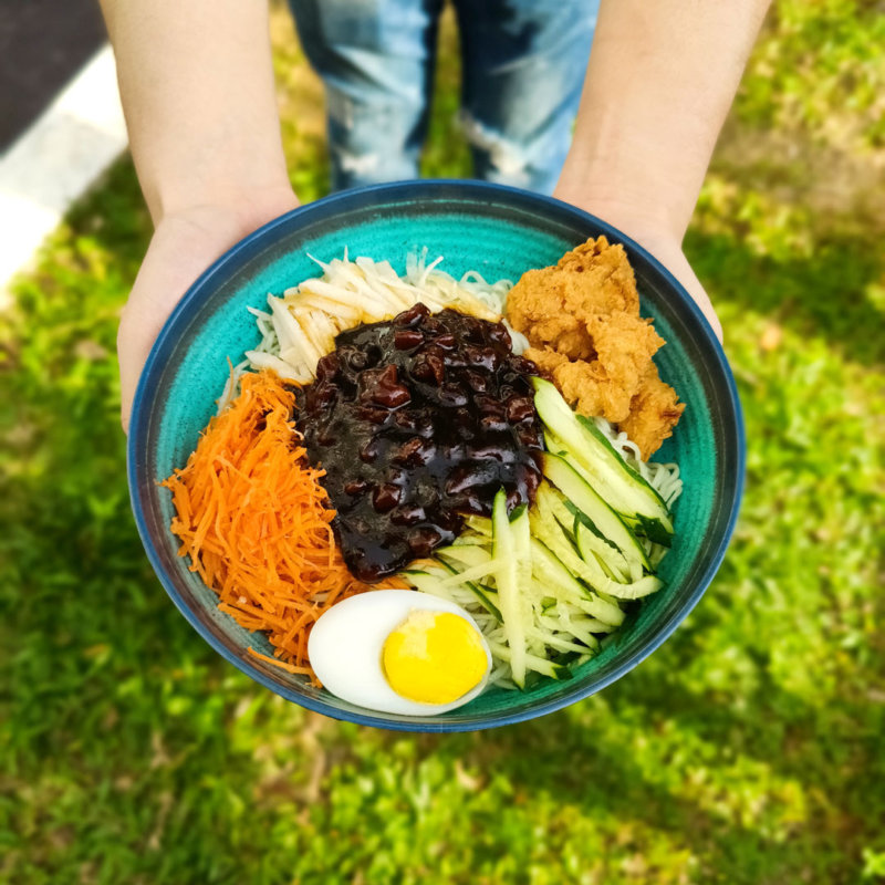 Image of flavory Soy-bean paste noodles served with Chicken Katsu and hard-boiled egg
